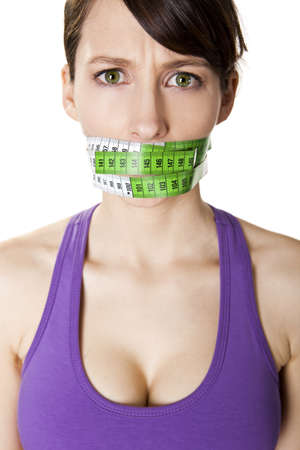Portrait of a young  woman with a green measuring tape covering the mouth Stock Photo - 9469059