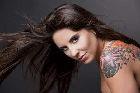 tatto: Portrait of a lovely woman with a tatto on the shoulder against a grey background and spread hair