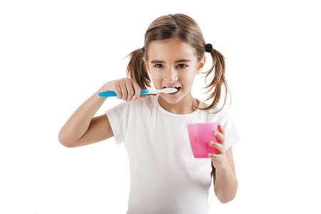 brush teeth: Little girl brushing teeth isolated on white background