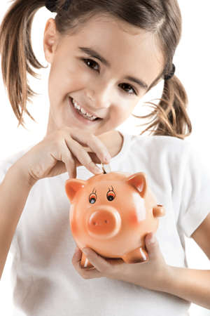 Little girl holding a piggy-bank and inserting a one euro coin photo