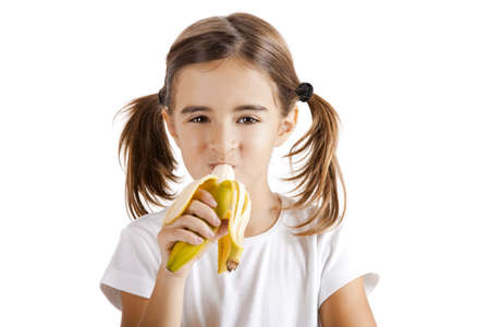 Portrait of a beautiful little girl eating a banana photo