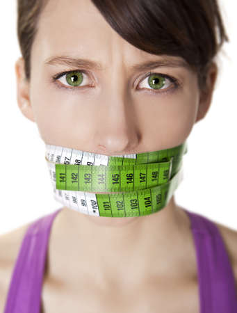 Portrait of a young  woman with a green measuring tape covering the mouth Stock Photo - 9523071