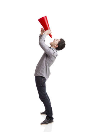Young man shouting into a megaphone over a white background  photo