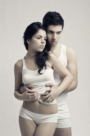 Beautiful and attractive young couple in underwear standing over a white background photo