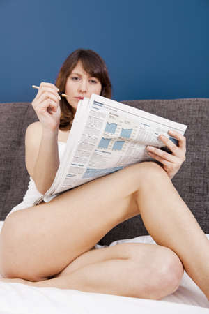 Beautiful young woman lying on the bed and seek for a job on the newspaper photo
