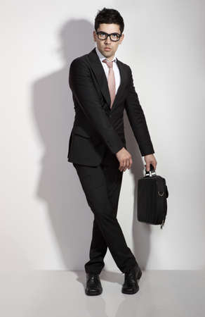 Portrait of a young and fashion businessman over a white background photo