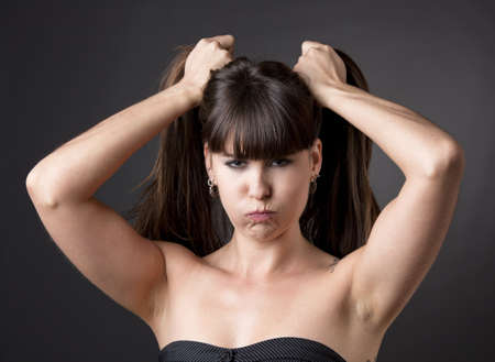 pulling hair: Portrait of a funny woman pulling hair upset with something, against a grey background