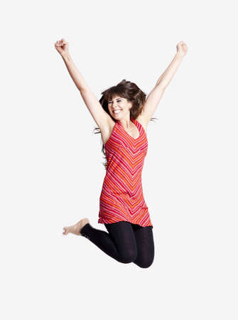 jumping: Beautiful happy woman jumping over a grey background