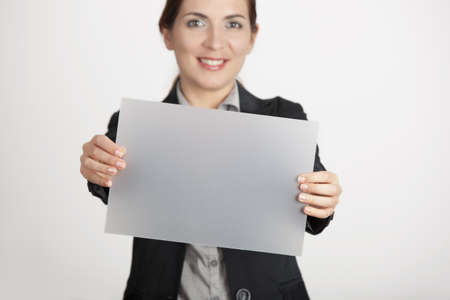 hold on: Beautiful business woman holding a blank translucid paper sheet Stock Photo