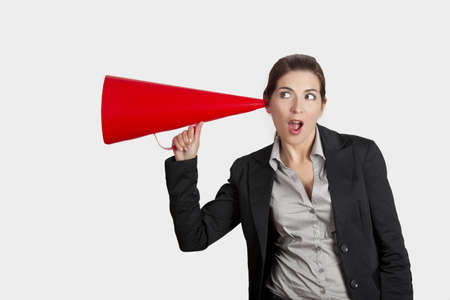 Business young woman speaking to a megaphone, over white background photo