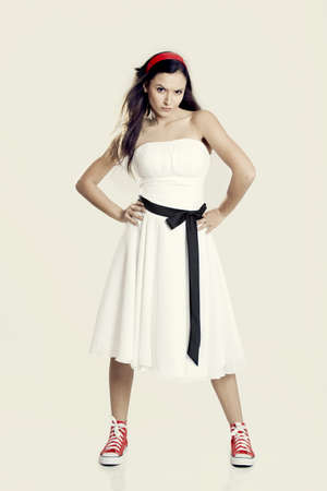 Beautiful young woman wearing a wonderful white dress and sneakers and with a upset expression photo