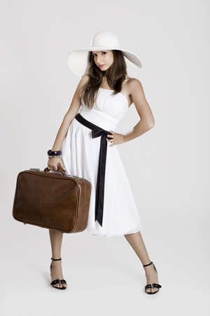 Fashion woman posing with a old suitcase and a white dress photo