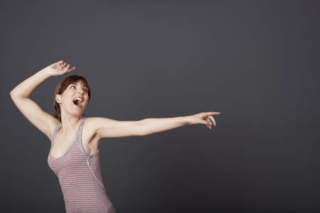 Happy young woman dancing and singing while listen music photo