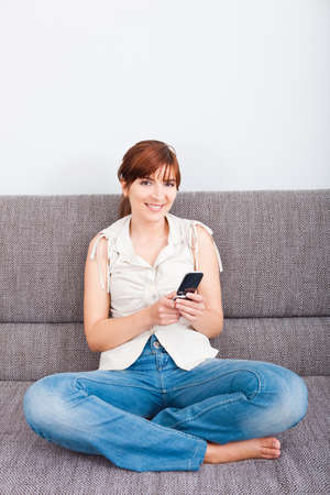 Beautiful woman seated on sofa holding a cellphone and sending a sms photo