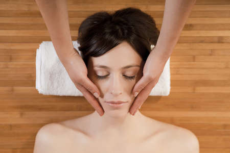 Beautiful and attractive woman on a spa receiving a face massage Stock Photo - 10010258