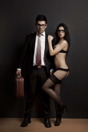 Business man embraced with a sexy young woman in lingerie. Concept about work and pleasure photo