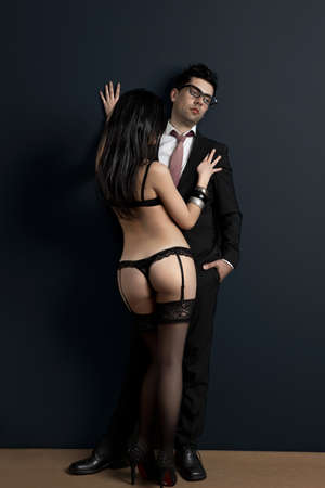 Tired and upset businessman with a sexy young woman in lingerie. Concept about work and pleasure photo