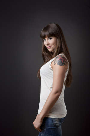 tattooed: Beautiful young woman standing over a grey backround Stock Photo