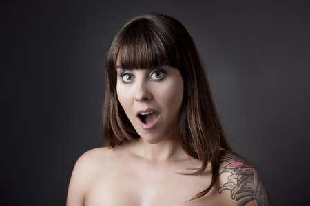 femme bouche ouverte: Portrait d'une belle femme avec une expression étonner sur un fond gris