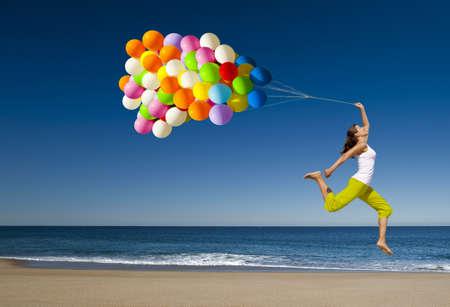 Chica hermosa y athletic con globos coloridos saltando en la playa  Foto de archivo