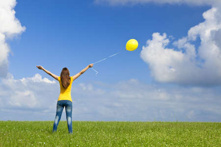 Happy young woman with a yellow balloon on a green meadow