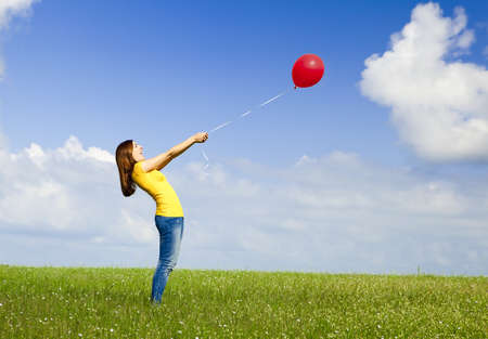 Happy young woman with a red balloon on a green meadow Stock Photo - 10010207