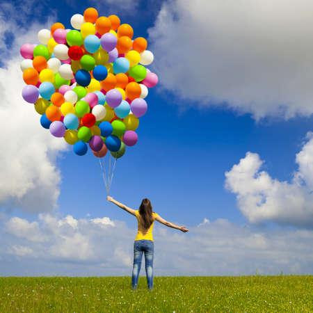 Happy young woman with colorful balloons on a green meadow Zdjęcie Seryjne - 10010257