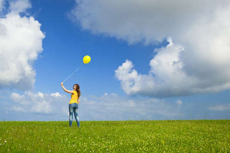 Happy young woman with a yellow balloon on a green meadow photo