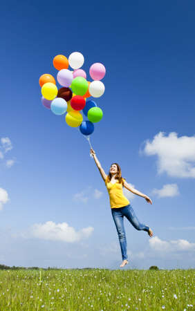 Happy young woman holding colorful balloons and flying over a green meadow
