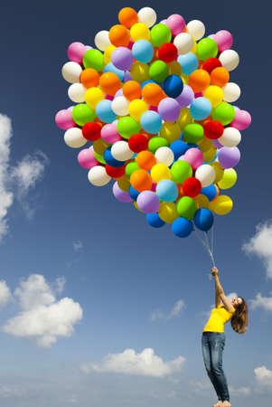 ballons: Heureuse jeune femme avec des ballons color�s sur un pr� vert