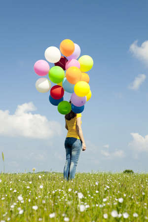 fluctuate: Happy young woman with colorful balloons on a green meadow