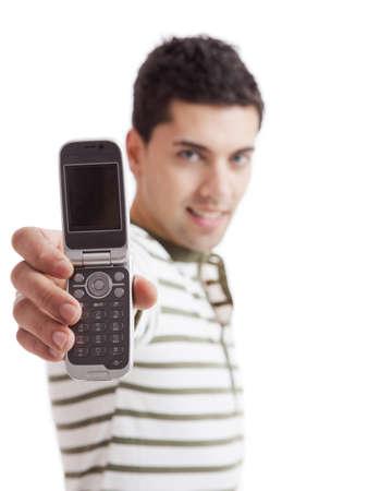 amigas conversando: Apuesto joven sosteniendo y mostrando un tel�fono celular, aislado en blanco. Foco est� en el tel�fono