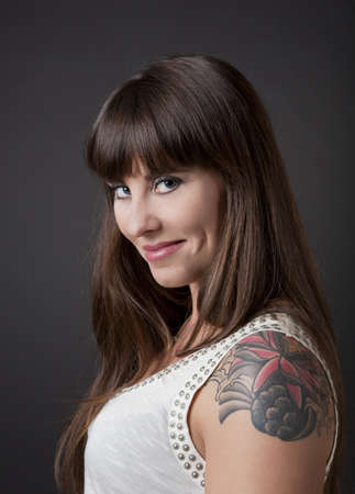 Portrait of a lovely woman with a tatto on the shoulder against a grey background Stock Photo - 10627204