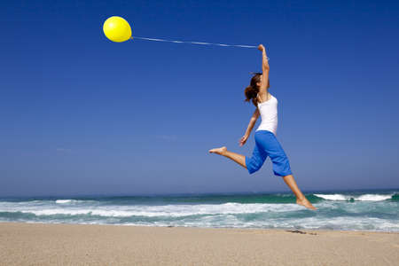 Beautiful and athletic Girl jumping with a balloon on the beach photo