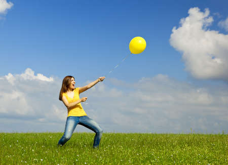 Happy young woman holding a yellow balloon with strenght photo