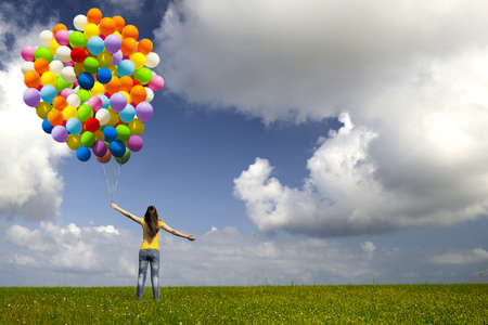 woman flying: Happy young woman with colorful balloons on a green meadow