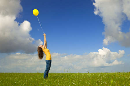 fluctuate: Happy young woman with a yellow balloon on a green meadow