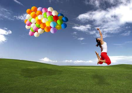 Chica hermosa y atlética salto con globos en un Prado verde Foto de archivo