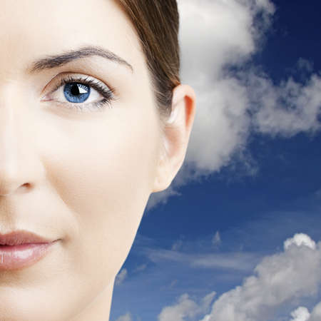 Close-up portrait of a beautiful young woman with  a cloudy sky on the background photo