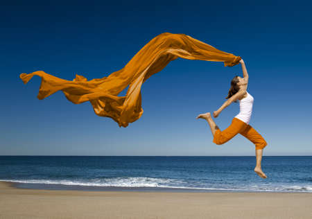 Beautiful young woman jumping on the beach with a colored tissue  photo