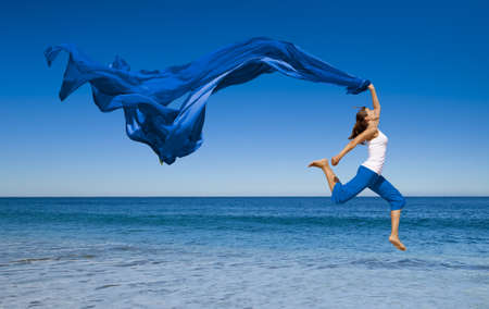 wellbeing: Beautiful young woman jumping on the beach with a colored tissue