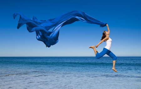Mooie jonge vrouw springen op het strand met een gekleurd weefsel