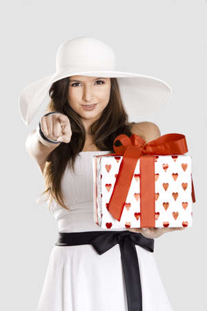 Beautiful and happy young woman holding a gift and pointing to you photo