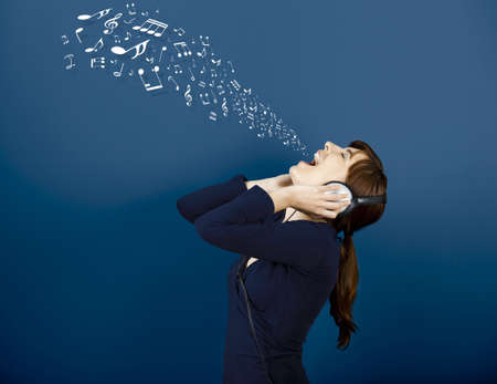 Young woman singing and listen music with musical notes getting out of her mouth photo