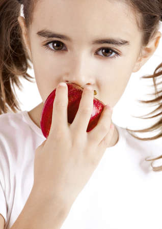 Portrait of a beautiful little girl eating a red apple photo