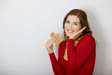 Beautiful young woman holding a gingerbread man cookie photo