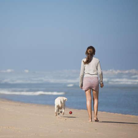perro labrador: Mujer joven caminaba con su perro en la playa Foto de archivo