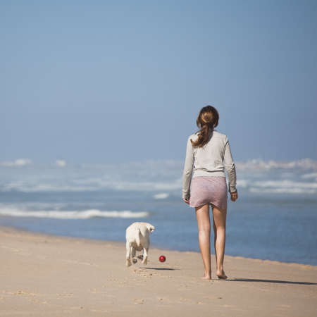 dog summer: Young woman walking with her dog on the beach Stock Photo