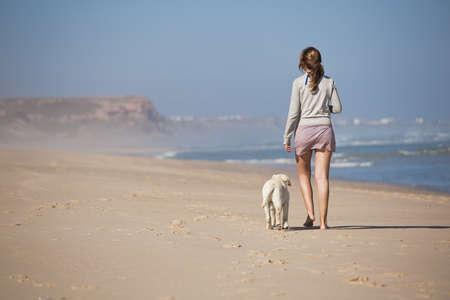 mujer con perro: Mujer joven caminaba con su perro en la playa Foto de archivo