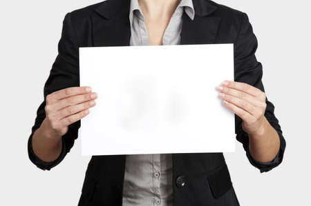 Woman holding a blank paper sheet with both hands photo